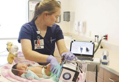 Nurse using Certascan baby footprint scanner